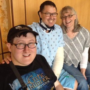 Professor Mark Newcom photographed with son, Stross, and wife, Joy, during a moment of his recovery from near fatal fall.