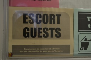 A reminder hangs on a dorm telling residents to escort guests as a form of campus security. Photo by Shannon Clark