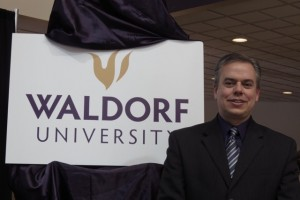 President Bob Alsop stands next to the new Waldorf University sign. Photo by Molly Maschka