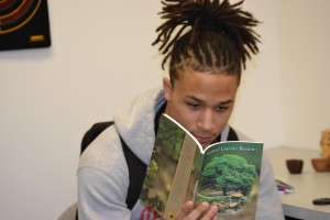 Waldorf student Vybert Greene takes a moment to read from the 2015 Waldorf Literary Review. Photo by Darien Walsh